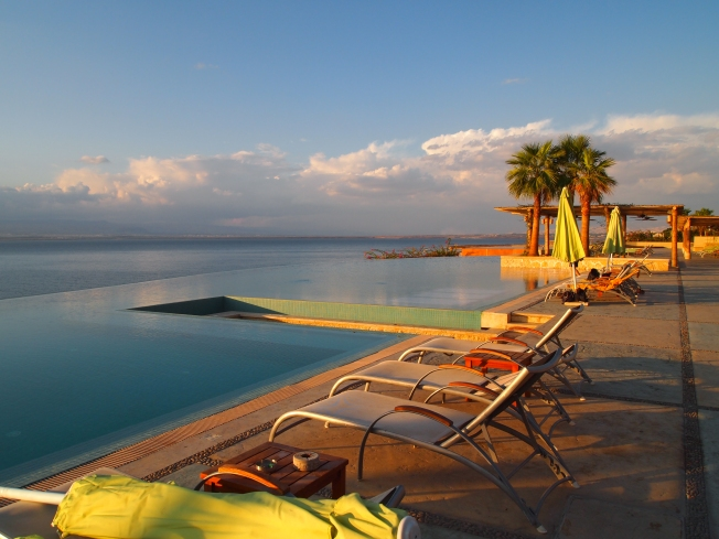 the infinity pool at the O Beach Hotel stretching into the Dead Sea